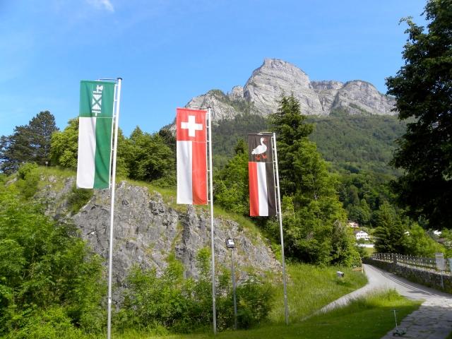 Widok z pagórka Splee na Gonzen. Między pierwszym i drugim szczytem widoczna kamienna figura. Flaga Kantonu St. Gallen, szwajcarska oraz flaga z gęsią Sargansu.